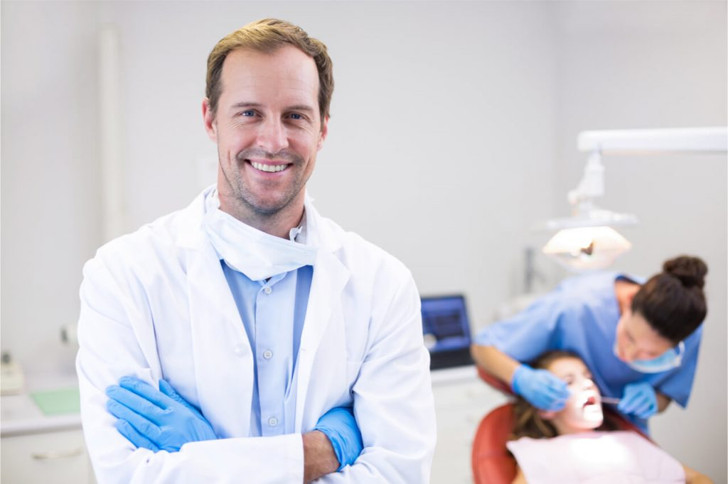 The dentist lets his assistant clean the patient's mouth.